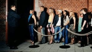 Nightlife people waiting in line to get into bar with bouncer