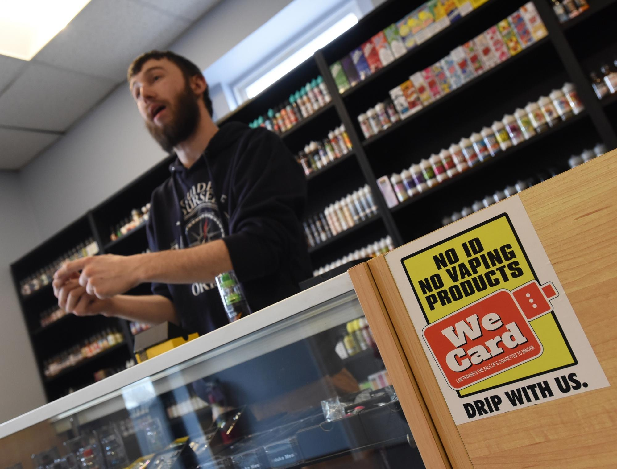Vape Shop Clerk Checking ID with We Card Sticker on Counter